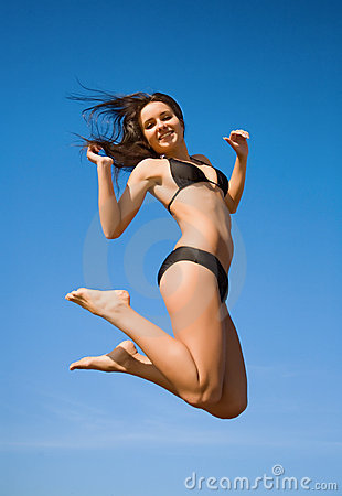 Woman in bikini jumping high