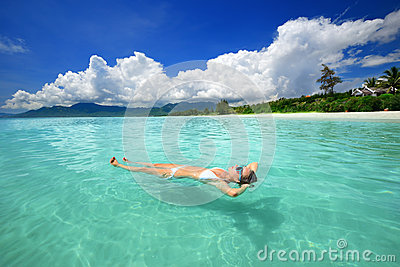 Woman in bikini relaxing lying on the water