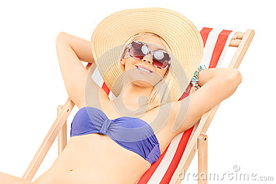 Woman in bikini relaxing on a sun lounger