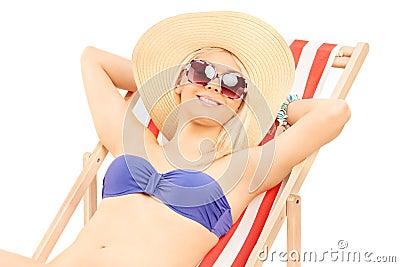 Woman in bikini relaxing on a sun lounger