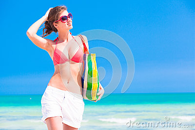 Woman in bikini and sunglasses with beach bag