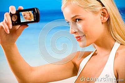 Woman in bikini taking photo