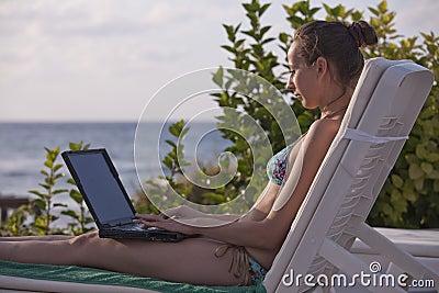 Woman in bikinis with laptop