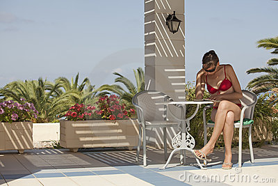 Woman in bikinis reading book