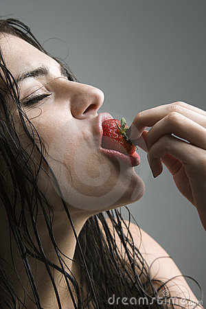 Woman biting strawberry.