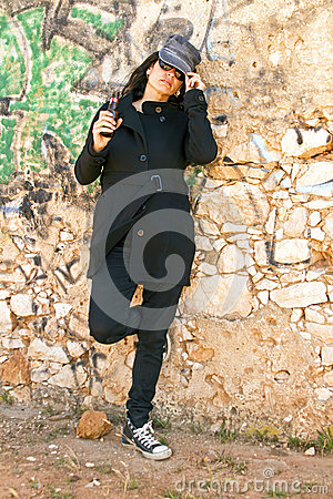 Woman in black at a brick wall