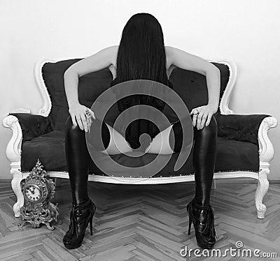 Woman in black corset sitting on sofa