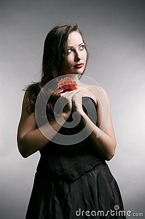 Woman in black dress holding flower