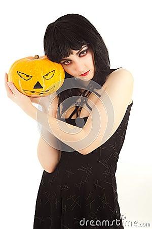 Woman in black dress holding a Jack-o -lantern
