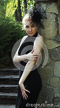 Woman in black dress near stone wall