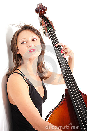 Woman in black dress play double bass by white wall