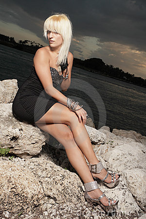 Woman in a black dress on the rocks