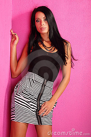 Woman with black hair stands near pink wall