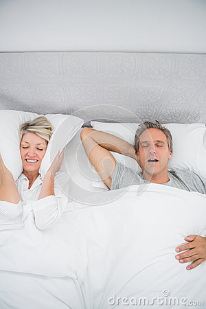 Woman blocking her ears because of partners snoring