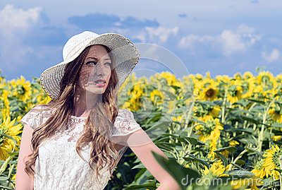 Woman on blooming sunflower field in summer
