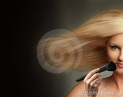 Woman with blowing hair and with make-up brush