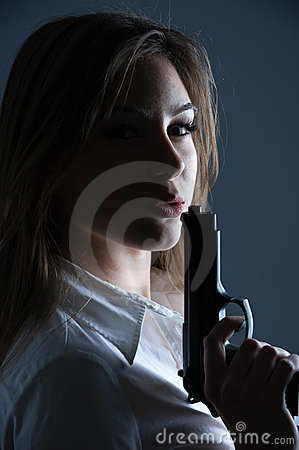 Woman blowing at her guns barrel
