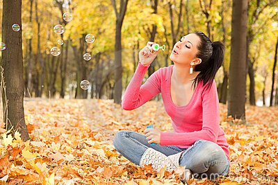 Woman blowing soap bubble in the autumn park