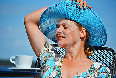 Woman with blue hat having coffee on the beach