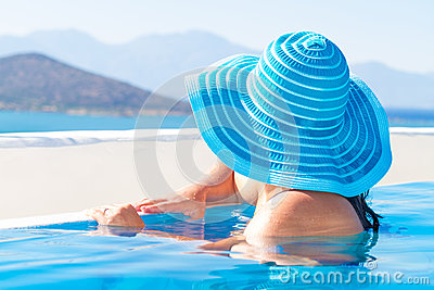 Woman in blue hat at the swimming pool