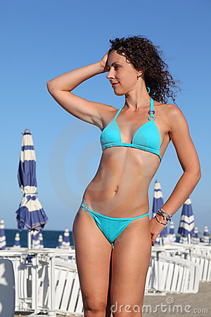 Woman in blue swimsuit stands on beach