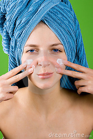Woman in blue towel applying facial cream