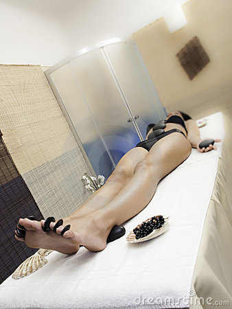 Woman body at spa with black stones
