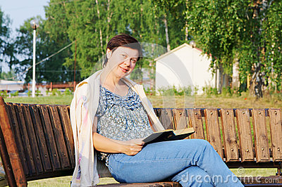 Woman with a book on a bench