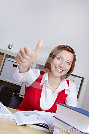 Woman with books holding thumbs up