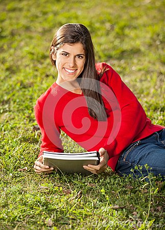Woman With Books Relaxing On Grass At College