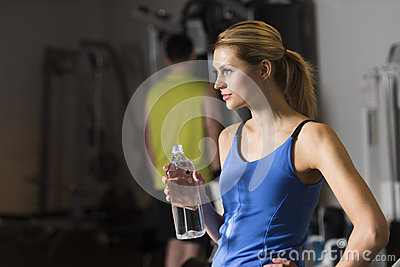 Woman With Bottle Of Water Looking Away At Gym