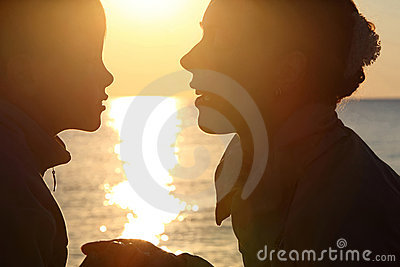 Woman with boy sit ashore opposite sun