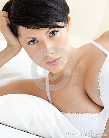 Woman in bra is lying in the bed