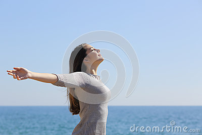 Woman breathing deep fresh air and raising arms