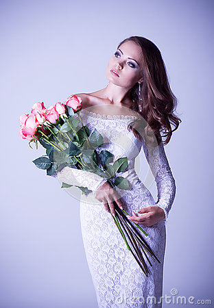 Woman in bridal dress with bouquet from roses