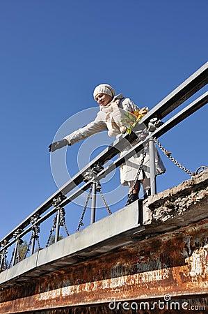 Woman on bridge throws maple leaf in water