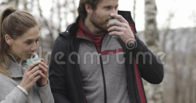 Woman bringing hot beverage or coffee or tea to man in camping place. Couple people in love autumn outdoor trip in. Nature. Fall sunny day. 4k slow motion video stock footage