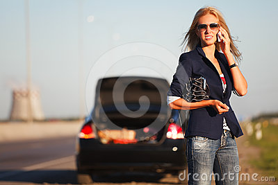 Woman with broken car calling on the phone