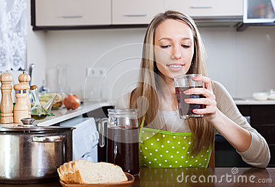 Woman   with brown beverage in glass