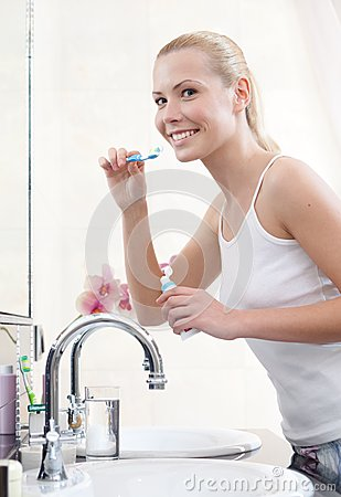 Woman brushes her teeth to keep it intact