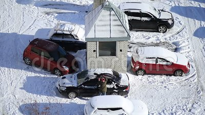 Woman brushing snow from car with snow brush stock footage