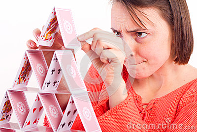 Attractive woman building house of cards