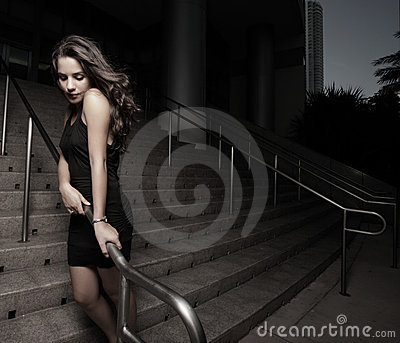 Woman by a building after dark