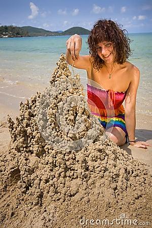 A woman building a sandcastle