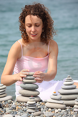 Woman builds stone stacks on pebble beach