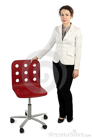 Woman in business dress standing near red armchair
