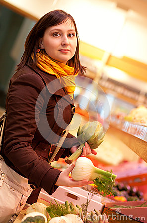 Woman buying artichokes and fennel bulbs at mark