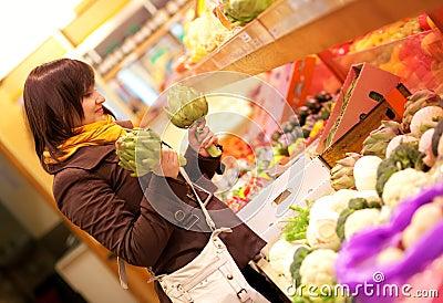 Woman buying artichokes at market