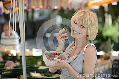 Woman buying strawberries at farmer s market