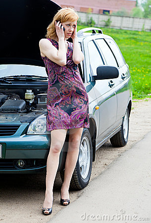 A woman is calling on a phone near the broken car